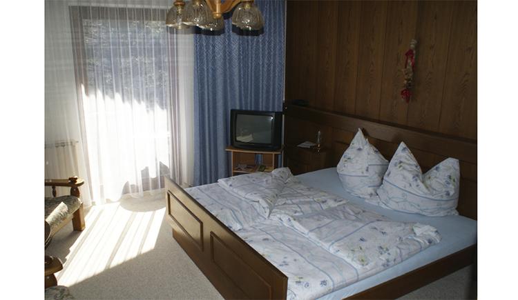 Schlafzimmer mit Doppelzimmer, im Hintergrund ein Fernseher und Balkontür