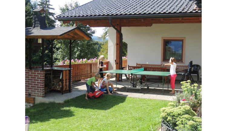 Kinder spielen Tischtennis vor dem Haus, Kinder auf kleinen Rutsch-Autos, Wiesen, Pflanzen
