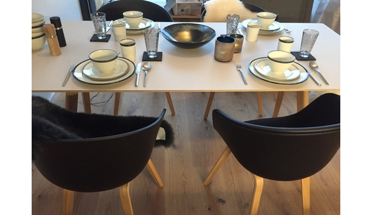 Table with plates and cups and four chairs