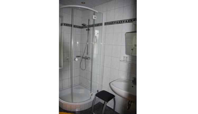 Badezimmer mit Dusche, Waschbecken, Hocker, Spiegel