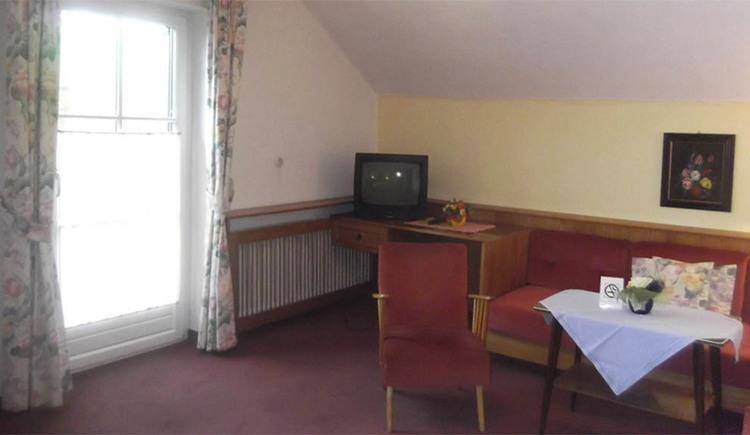 Sessel, Tisch und Bank, Fernseher steht im Eck, seitlich eine Balkontür, Teppichboden