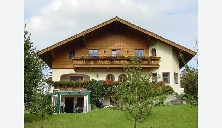im Hintergrund das Haus mit Balkonblumen, im Vordergrund Wiese, Bäume