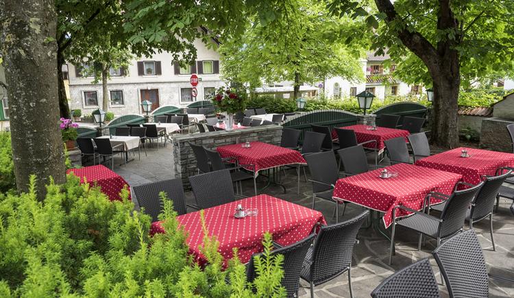 Gastgarten mit rot gedeckten Tischen und Bäumen