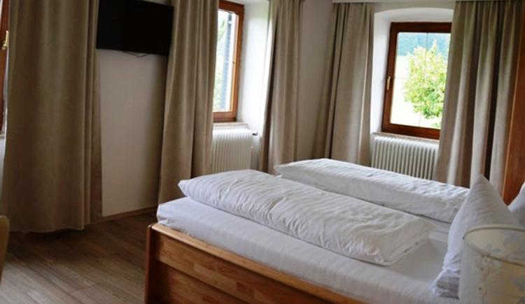 Schlafzimmer mit Doppelbett, im Hintergrund Fenster
