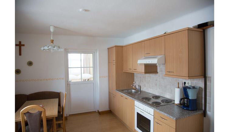 Blick in die Küche mit Herd, Kaffeemaschine, im Hintergrund ein Fenster, Tisch und Stühle