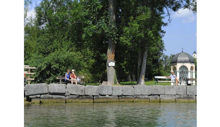 Blick vom See auf das Ufer, Personen sitzen auf einer Bank, im Hintergrund Bäume, seitlich eine kleine Seekapelle