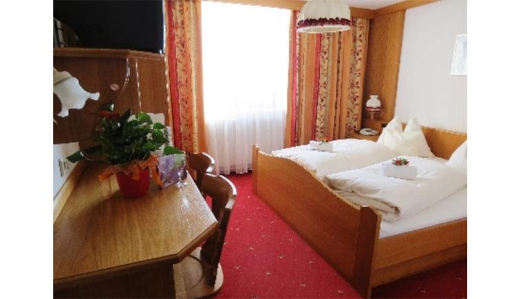 Schlafzimmer mit Doppelbett, im Hintergrund, Fenster, seitlich ein Tisch und Stühle
