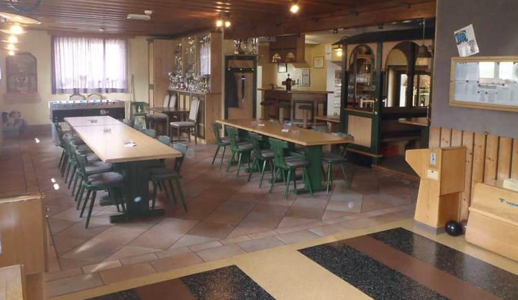 Innenbereich mit Tischen und Stühlen, im Hintergrund der Barbereich
