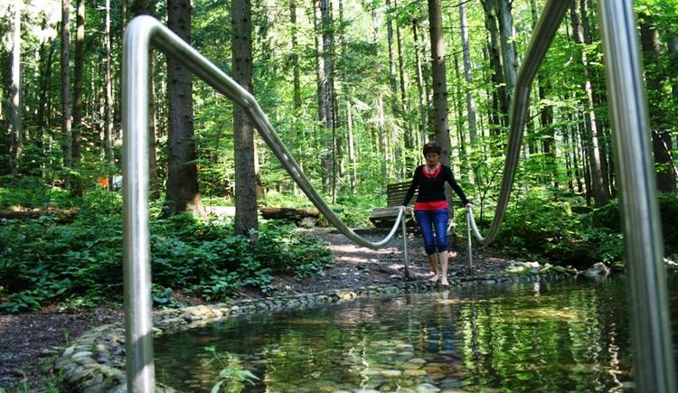 Wasserbecken gefüllt mit Steinen und einer Dame die durchwatet. (© Ferienregion Böhmerwald)