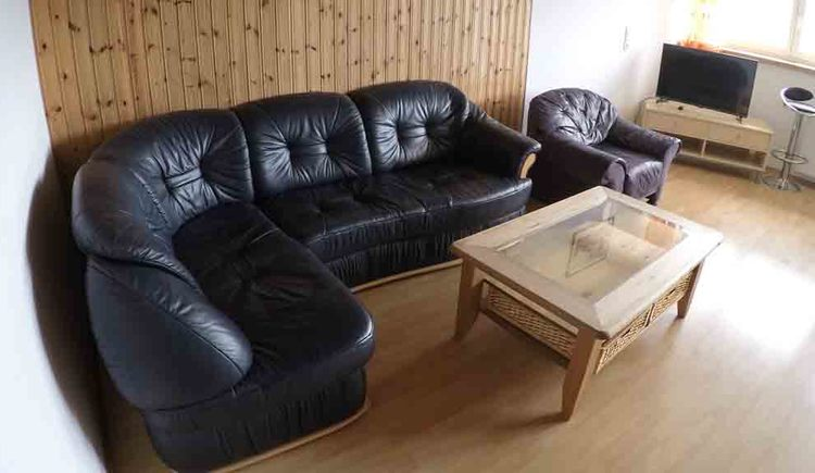 living area with a Couch made of leather, chair, table, in the background a TV, bar stool, window\n