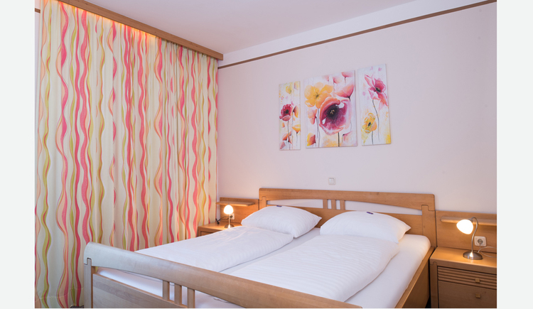 Doppelbett, Nachtkästchen, Tischlampen, im Hintergrund ein Bild ober dem Bett