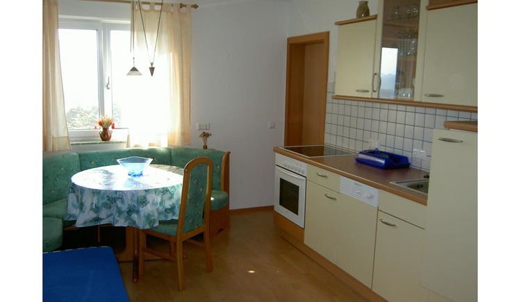 kitchen with sink and cooker on the side, table, corner bench and chairs in the background, window