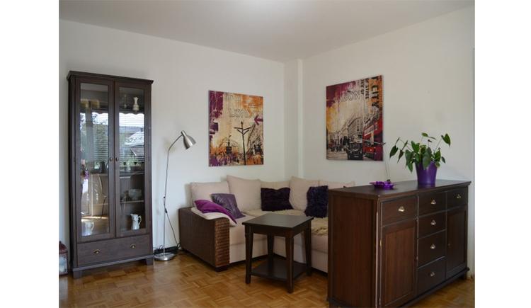 Wohnbereich mit Spiegelschrank, Eckcouch, Tisch und einer Kommode