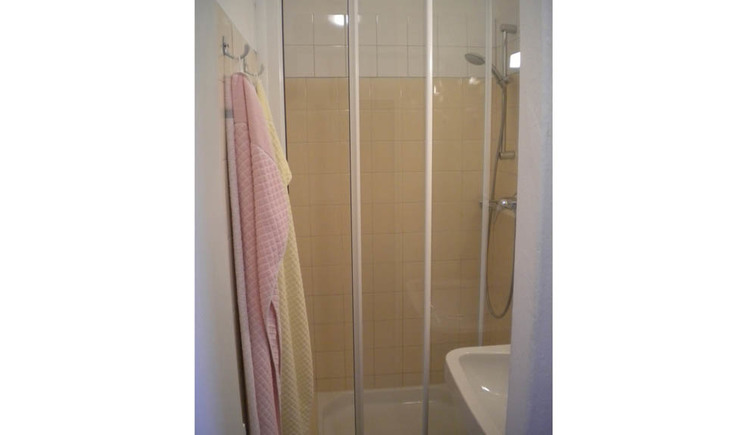 Bathroom with shower, on the side hanging towels