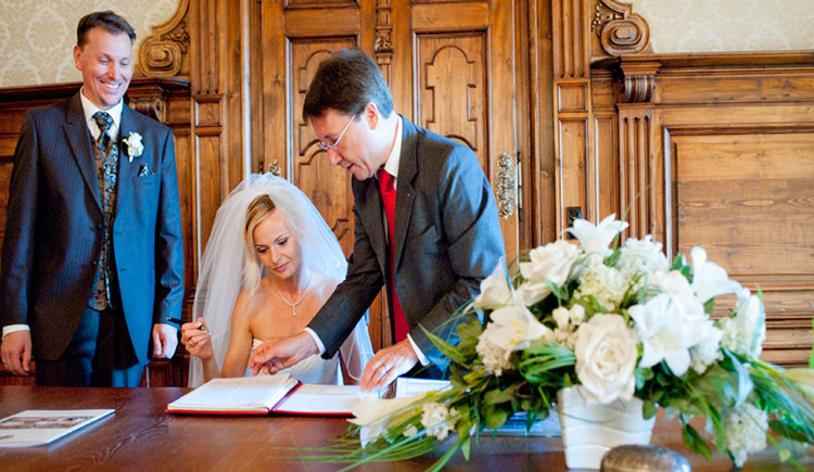 Eine Braut unterschreibt die Heiratsurkunde, neben ihr stehen der Standesbeamte und der Bräutigam