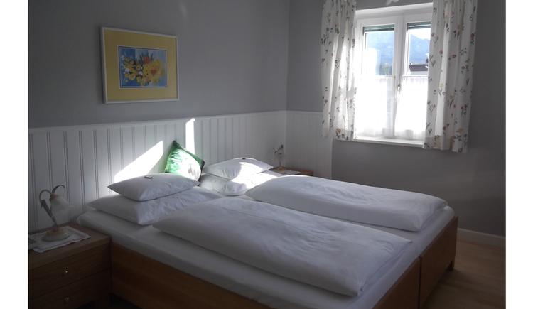 Schlafzimmer mit Doppelbett, Nachtkästchen mit Tischlampen, hinter dem Bett ein Bild, im Hintergrund ein Fenster