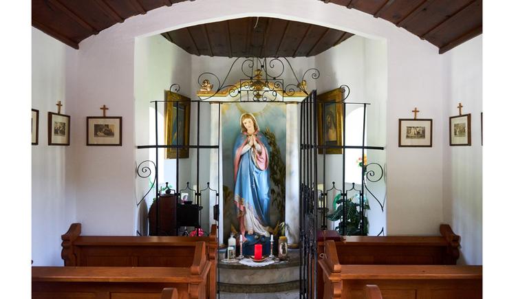 seitlich Holzbänke, im Hintergrund eine Marienstatue, Kerzen, seitlich an der Wand Bilder