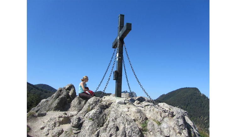 person is sitting on a stone next to the cross of the Almkogel\n