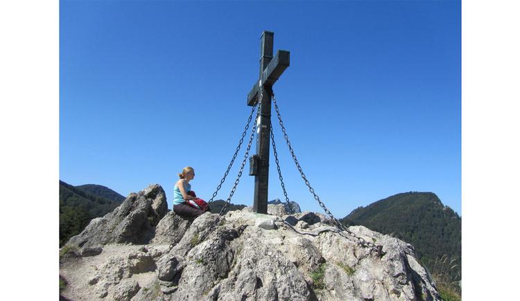 Person sitzt beim Gipfelkreuz auf den Steinen