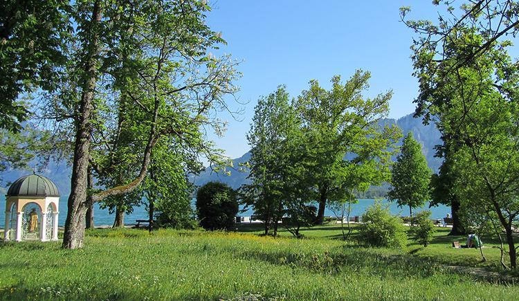 Parklandschaft an der Seepromenade in Mondsee im Hintergrund der Mondsee. Links im Bild erkennbar die Judas Thaddäus Kapelle. (© www.mondsee.at)