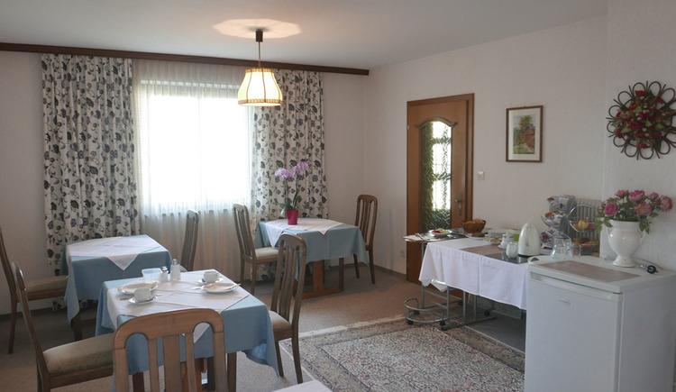 Tische mit Stühle, im Hintergrund Tisch mit Frühstücksbuffet, seitlich ein Fenster