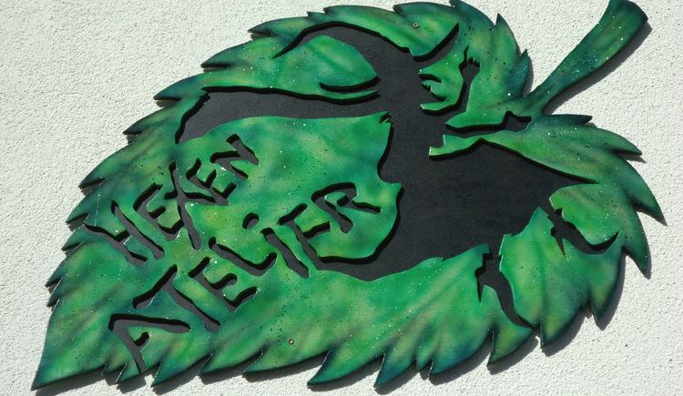 Hier sehen Sie das Logo vom Hexen Atelier - ein grünes Baumblatt mit Aufschrift und Zeichnung