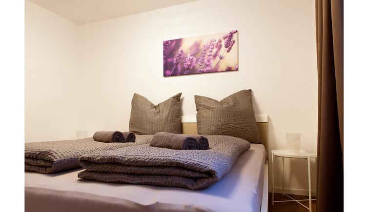 Schlafzimmer, Doppelbett, kleiner Tisch mit Stehlampe seitlich