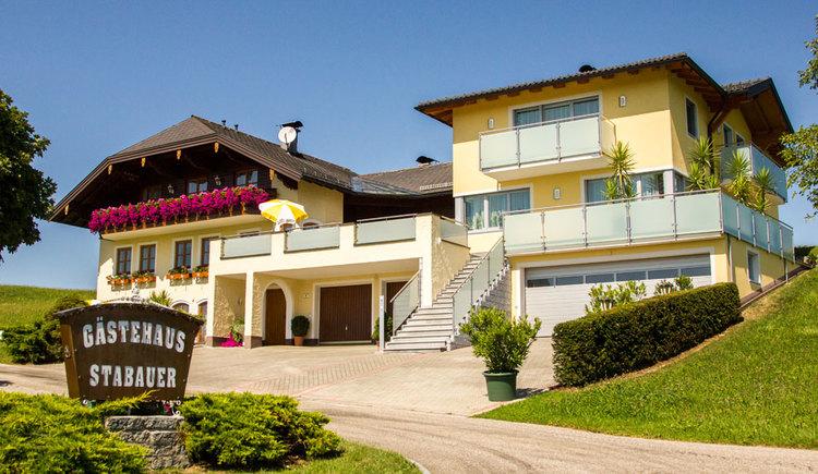 Blick auf das Haus mit Balkonblumen, Terrasse, im Vordergrund die Einfahrt, Wiesen