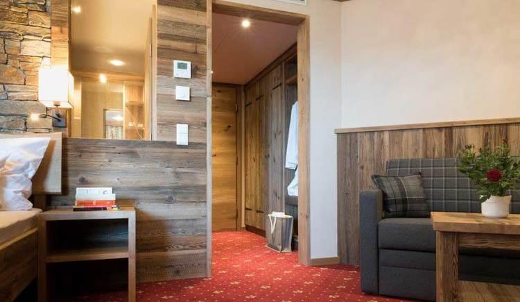 Blick von einem Hotelzimmer Richtung Vorraum und Tür, auf der Seite sieht man einen Tisch mit Sofa, auf der anderen Seite das Nachtkästchen und einen Teil des Bettes