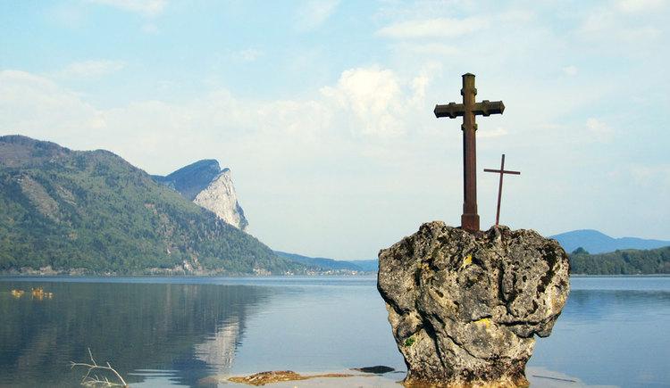Kreuzstein im See, im Hintergrund Berge