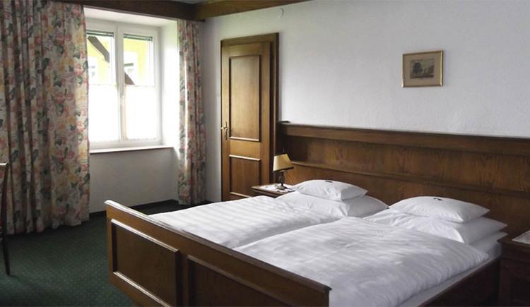 Schlafzimmer mit Doppelbett, im Hintergrund seitlich ein Fenster, Teppichboden