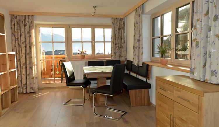 Wohnraum mit großem Tisch, Sesseln und Eckbank mit Blick auf Balkon