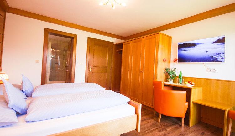 Schlafzimmer mit Doppelbett, seitlich ein Tisch mit einer Falsche und Glas, gemütlicher Sessel, im Hintergrund Blick in das Badezimmer, Schrank\n\n
