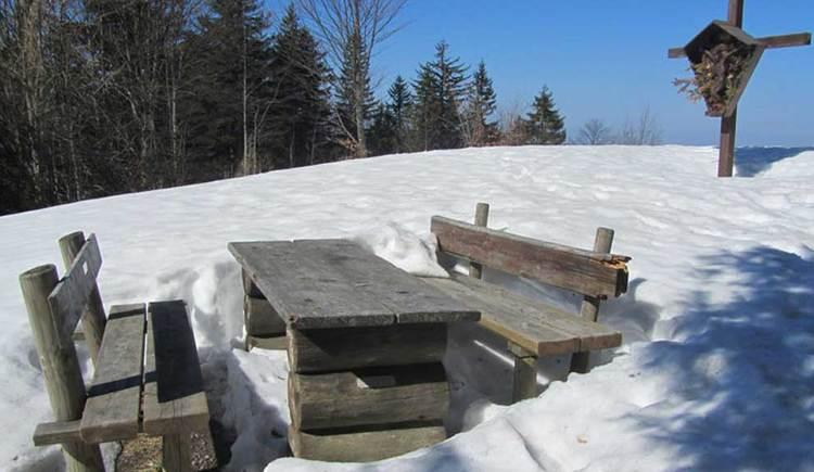 Blick auf einen Tisch und zwei Bänke, im Hintergrund ein Wald, rundherum eine schneebedeckte Wiese