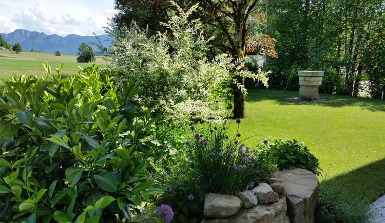 Blick in den Garten, Sträucher, im Hintergrund Berge. (© Tourismusverband MondSeeLand)