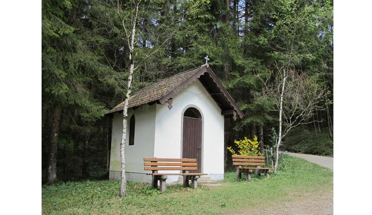Blick auf die Kapelle, im Hintergrund Bäume, im Vordergrund Sitzbänke