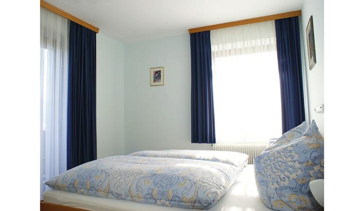 Schlafzimmer mit Doppelbett, im Hintergrund und seitlich Fenster