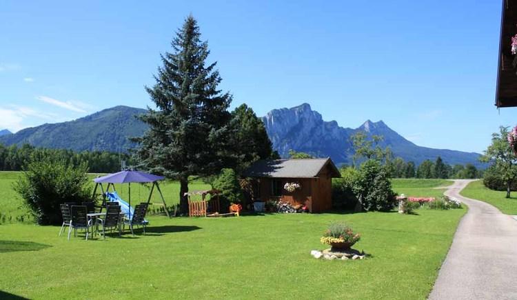 Garten mit Hütte, Rutsche, Tisch und Stühle, Blumen, im Hintergrund die Berge