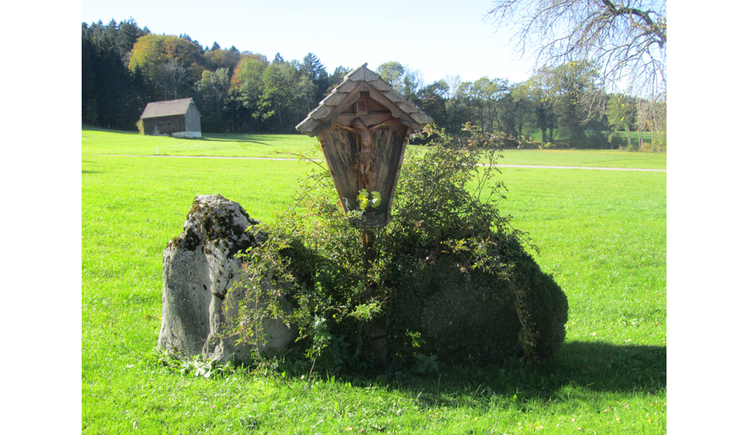 View of a wooden cross surrounded by stones in a meadow, in the background a forest