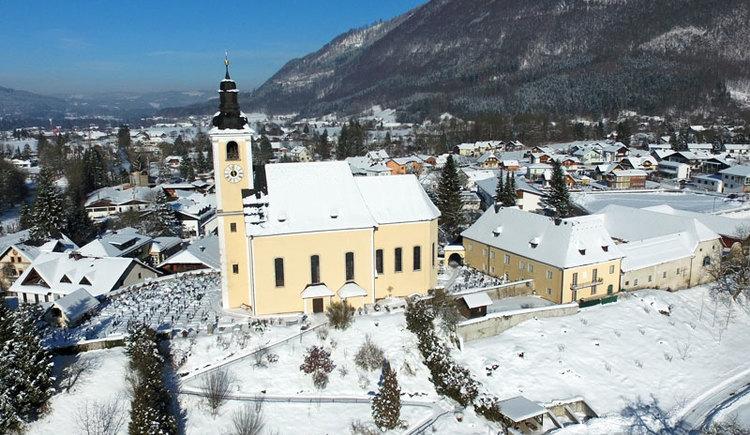 Das Bergsteigerdorf Grünau im Almtal im Winter mit Blick über die Pfarrkirche auf das nördliche Almtal