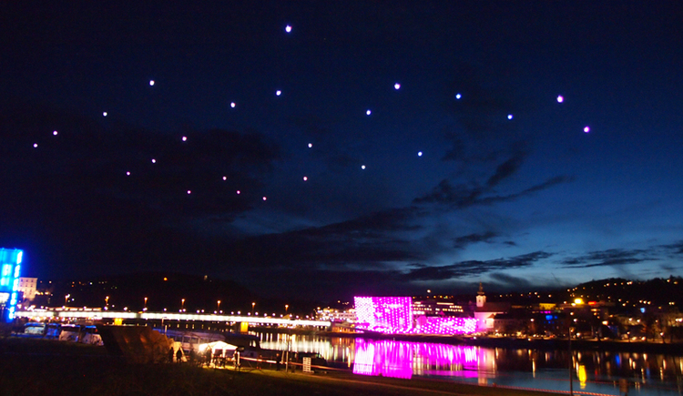Blick aus der Ferne auf das pink-farbene Außenfassade des Ars Electronica Center bei Nacht. (© Martin Hieslmair)