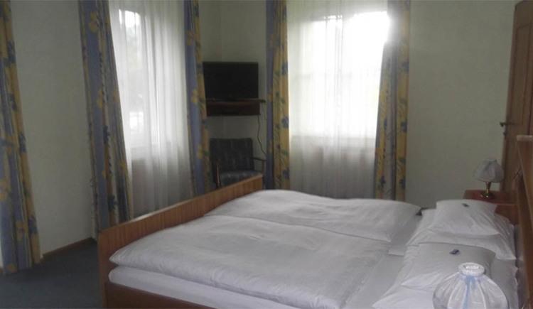 Schlafzimmer mit Doppelbett, im Hintergrund Fenster und ein Fernseher auf der Wand montiert, darunter ein Sessel