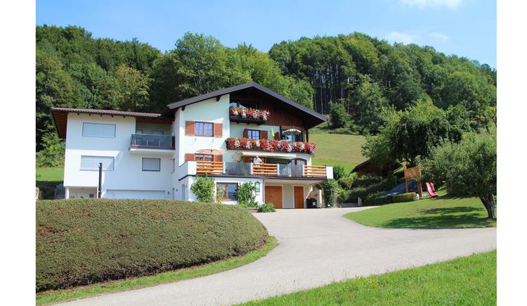 Blick auf das Haus mit Balkon, Blumen, im Hintergrund ein Wald, Wiesen