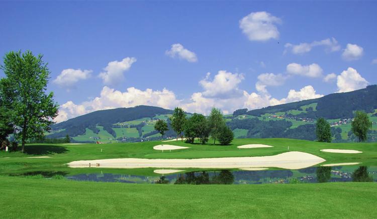 Blick auf den Golfplatz, Wiese, Bäume, im Hintergrund Landschaft