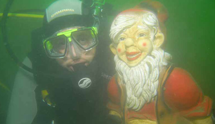 Diver with a garden gnome underwater