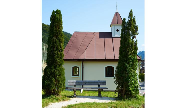 Blick auf die Kapelle, seitlich Bäume, im Vordergrund eine Holzbank
