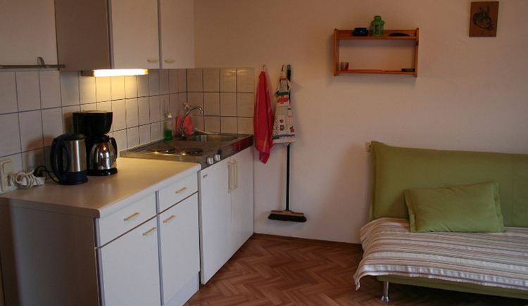 kitchen corner with kettle, coffee machine, cooker, sink, couch on the side