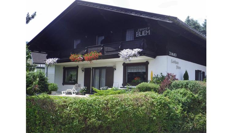 Blick auf das Haus mit Balkon und Blumen, vor dem Haus eine Gartenliege, im Vordergrund eine Hecke