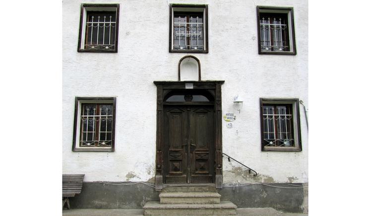 Blick auf ein Haus mit vergitterten Fenstern, Holzhaustüre