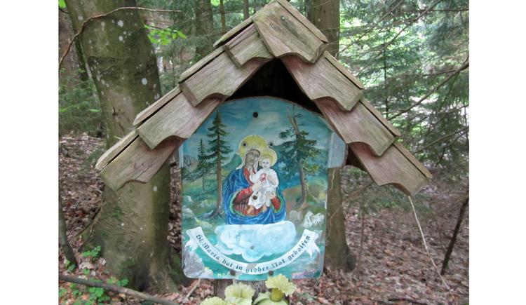 Blick auf ein Holzmarterl mit einem Heiligenbild, im Hintergrund ein Wald
